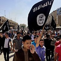FILE - In this June 16, 2014. file photo, demonstrators chant pro-Islamic State group slogans as they carry the group's flags in front of the provincial government headquarters in Mosul, Iraq. (AP Photo, File)