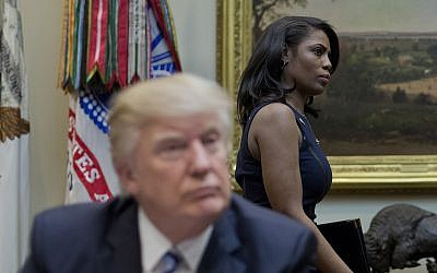 Then White House Director of communications for the Office of Public Liaison Omarosa Manigault, right, walks past President Donald Trump during a meeting on healthcare in the Roosevelt Room of the White House in Washington, March 13, 2017. (AP Photo/Pablo Martinez Monsivais)
