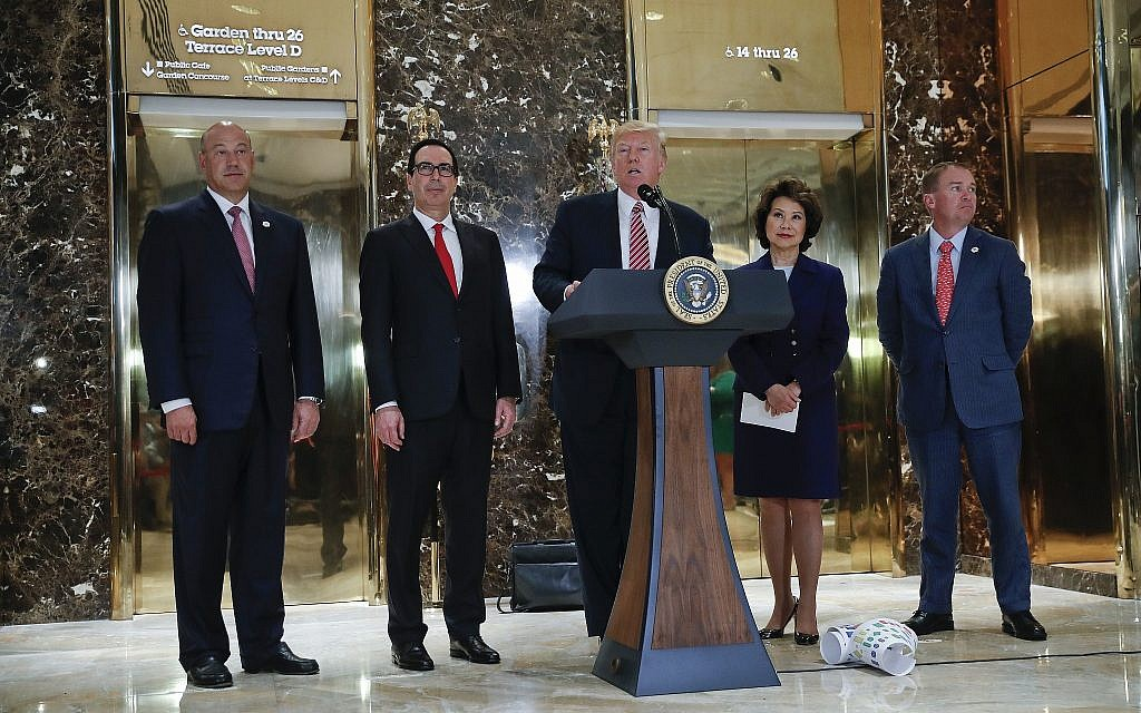 President Donald Trump speaks to the media in the lobby of Trump Tower, Tuesday, Aug. 15, 2017 in New York. With Trump are from l-r., National Economic Council Director Gary Cohn, Treasury Secretary Steven Mnuchin, Transportation Secretary Elaine Chao and OMB Director Mick Mulvaney. (AP Photo/Pablo Martinez Monsivais)