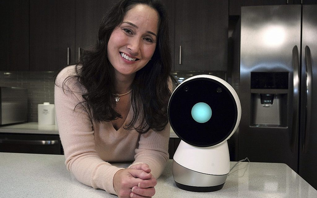 In this November 21, 2017, photo Massachusetts Institute of Technology robotics researcher Cynthia Breazeal, left, stands next to social robot Jibo, right, at the company's headquarters in Boston. (AP Photo/Steven Senne)