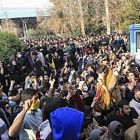 Illustrative. University students attend a protest inside Tehran University while anti-riot Iranian police prevent them to join other protestors, in Tehran, Iran, December 30, 2017. (AP Photo, obtained by The Associated Press outside of Iran)