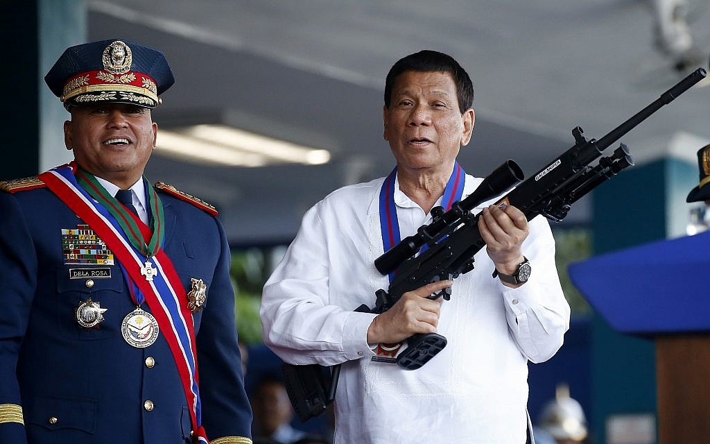 """Philippine President Rodrigo Duterte jokes to photographers as he holds an Israeli-made Galil rifle which was presented to him by outgoing Philippine National Police Chief Director General Ronald """"Bato"""" Dela Rosa, left, at the turnover-of-command ceremony on April 19, 2018, at Camp Crame in suburban Quezon city northeast of Manila, Philippines. (AP Photo/Bullit Marquez)"""