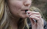 Illustrative: An unidentified 15-year-old high school student uses a vaping device (AP Photo/Steven Senne)