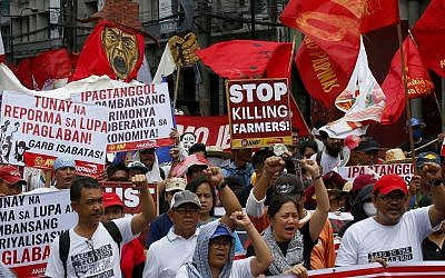 Protesters shout slogans as they march towards the Presidential Palace for a rally to demand genuine land reform and to protest the killings of about two dozen farmers in less than two years under his administration Friday, June 8, 2018 in Manila, Philippines. (AP Photo/Bullit Marquez)
