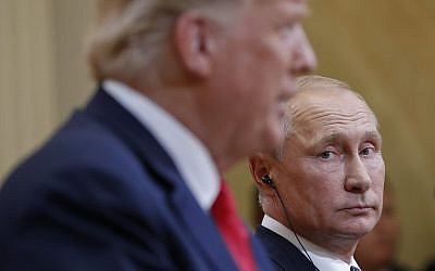 Russian President Vladimir Putin (right) looks over toward US President Donald Trump, as Trump speaks during their joint news conference in Helsinki, Finland, July 16, 2018. (AP/Pablo Martinez Monsivais)