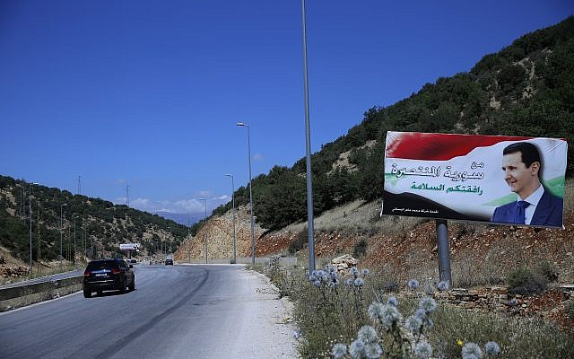 """In this July 20, 2018, photo, a poster of President Bashar Assad with Arabic that reads """"Welcome in victorious Syria."""" is seen on the border between Lebanon and Syria. (AP Photo/Hassan Ammar)"""