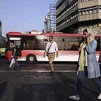 People cross Jomhouri-e-Eslami Street in downtown Tehran, Iran, Monday, July 30, 2018. (AP/Vahid Salemi)