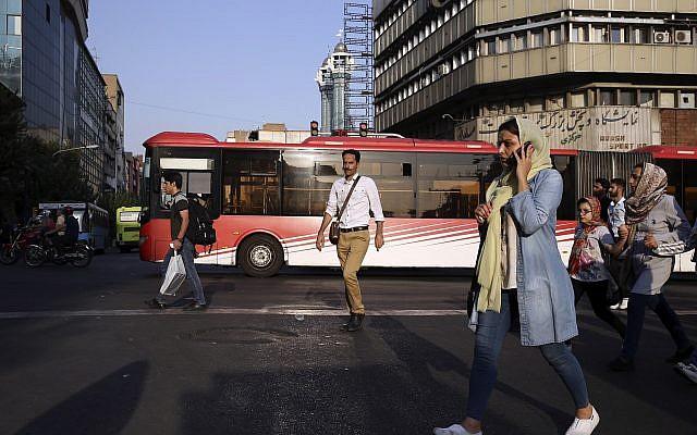 People cross Jomhouri-e-Eslami Street in downtown Tehran, Iran, Monday, July 30, 2018. (AP/Vahid Salemi)