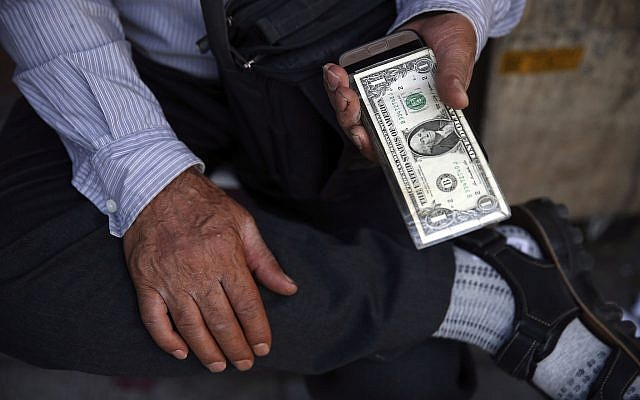 An Iranian street money exchanger holds US banknote in downtown Tehran, Iran, July 30, 2018 (AP Photo/Vahid Salemi)