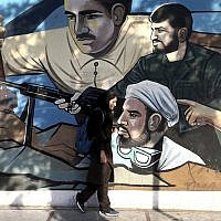 An Iranian woman walks past a mural depicting members of Basij paramilitary force, portraying Iranians' solidarity against their enemies, painted on the wall of a government building at the Felestin (Palestine) Sq. in downtown Tehran, Iran, July 30, 2018 (AP Photo/Ebrahim Noroozi)