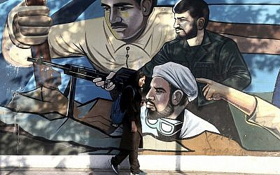 An Iranian woman walks past a mural depicting members of Basij paramilitary force, portraying Iranians' solidarity against their enemies, painted on the wall of a government building at Felestin (Palestine) Square in downtown Tehran, Iran, July 30, 2018 (AP Photo/Ebrahim Noroozi)