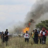 Red Cross workers and rescue workers carry an injured person on a stretcher, right, as airline workers, left, walk away from the site where an Aeromexico airliner crashed in a field near the airport in Durango, Mexico, July 31, 2018 (Red Cross Durango via AP)