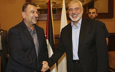 In this photo released by the Hamas Media Office, Ismail Haniyeh, right, the head of the Hamas political bureau, shakes hands with his deputy Saleh el-Arouri upon his arrival in Gaza from Cairo, Egypt, in Gaza City, Thursday, Aug. 2, 2018. (Mohammad Austaz/Hamas Media Office via AP)