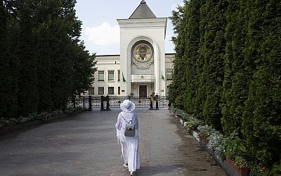 A woman walks toward the Russian Orthodox Church headquarters in the St. Daniel Monastery in Moscow, Russia, Aug. 3, 2018. (AP Photo/Pavel Golovkin)