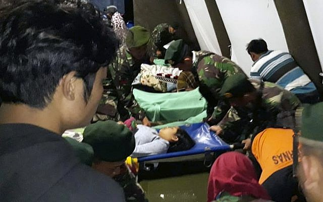 Indonesian soldiers tend to a woman injured in the earthquake at a makeshift hospital in Lombok, Indonesia Aug. 5, 2018. (AP Photo)