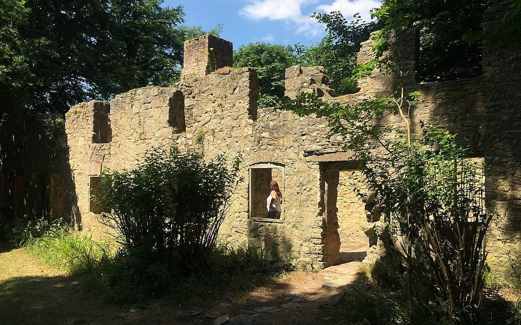 A visitor inspects the interior of a ruined cottage in the abandoned village of Tyneham, in Dorset, England, July 8, 2018. (Jerry Harmer/AP)