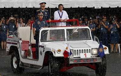 President Rodrigo Duterte, right, reviews the police under a sudden downpour to mark the 117th Philippine National Police Service anniversary at Camp Crame in suburban Quezon city northeast of Manila, Philippines. Wednesday, August 8, 2018. (AP/Bullit Marquez)