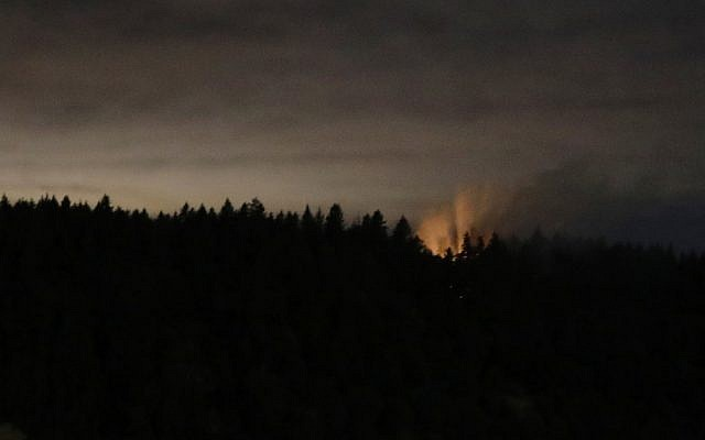 In this long-exposure photo, smoke and an orange glow are seen on Ketron Island in Washington state, early Saturday, Aug. 11, 2018 as viewed from near Steilacoom, Washington. (AP Photo/Ted S. Warren)