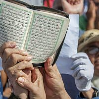 A person holds a copy of the Quran during a demonstration in Tunis, August 11, 2018. (AP Photo/Hassene Dridi)