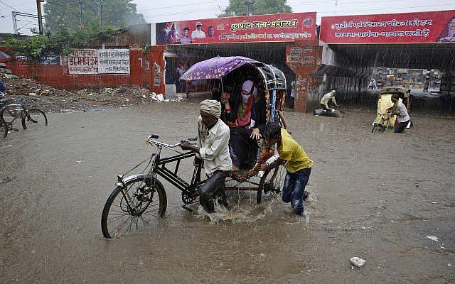 An Indian rickshaw puller makes way through a water logged street following heavy rains in Allahabad, India, August 12, 2018. (AP Photo/Rajesh Kumar Singh)
