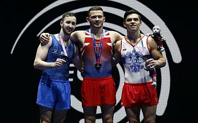 Dominick Cunningham of Great Britain, center, celebrates after winning gold in the floor exercise during the men's artistic gymnastics finals at the European Championships in Glasgow, Scotland, August 12, 2018. At left is Artem Dolgopyat of Israel who won silver and right is Artur Dalaloyan of Russia who won bronze. (AP Photo/Darko Bandic)