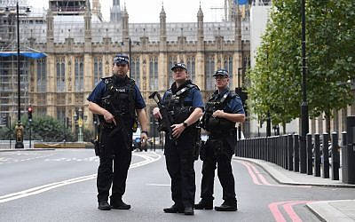 Armed police on Victoria Embankment in Westminster, after a car crashed into security barriers outside the Houses of Parliament, in London, August 14, 2018. (Stefan Rousseau/PA via AP)