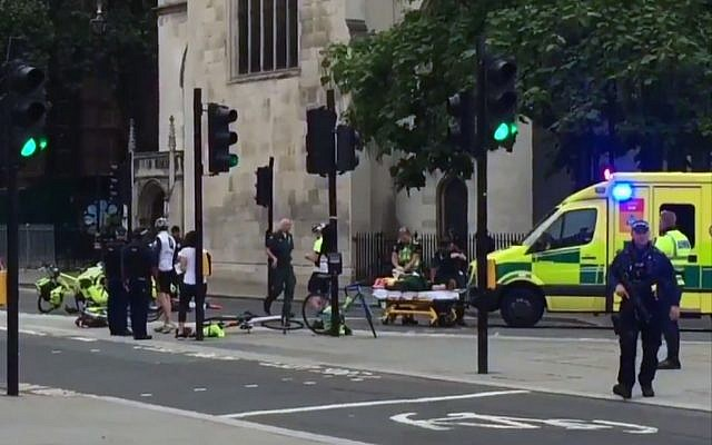 In this frame grab provided by UK Newsflare, emergency services attend the wounded after a car crashed into security barriers outside the Houses of Parliament in London, August 14, 2018. (UK Newsflare via AP)