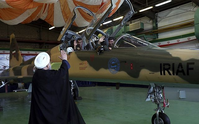 In this photo released by the official website of the office of the Iranian Presidency, President Hassan Rouhani, left, waves to the pilots of a fighter jet, before an inauguration ceremony of the aircraft, Iran, Tuesday, Aug. 21, 2018. (Iranian Presidency Office/AP)
