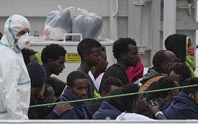 Migrants stand aboard the Italian Coast Guard ship Diciotti, moored at the Catania harbor, Aug. 21, 2018 (AP Photo/Salvatore Cavalli)
