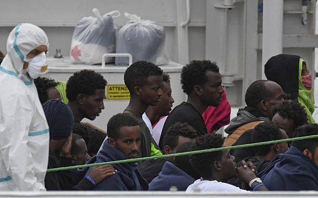 Migrants stand aboard the Italian Coast Guard ship Diciotti, moored at the Catania harbor, Aug. 21, 2018 (AP Photo/Salvatore Cavalli)
