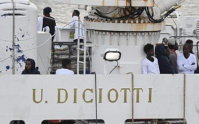Migrants stand on the deck of the Italian Coast Guard ship Diciotti, moored at the Catania harbor, Aug. 21, 2018 (AP Photo/Salvatore Cavalli)