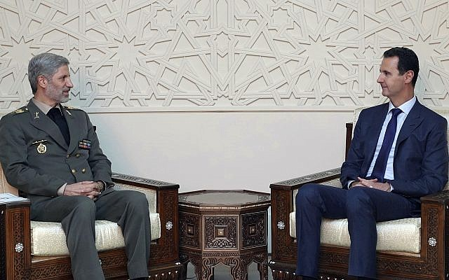 This photo released by the Syrian official news agency SANA, shows Syrian president Bashar Assad, right, meets with Iran's Defense minister Amir Hatami, in Damascus, Syria, Sunday, Aug. 26, 2018. Iran has provided key support to Assad in the seven-year civil war, sending thousands of military advisers and allied militiamen to bolster his forces. (SANA via AP)