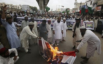 Pakistani protesters burn representation of Dutch flags during a protest to condemn the planned anti-Islam cartoon contest, in Karachi, Pakistan, on August 30, 2018. (AP/Fareed Khan)