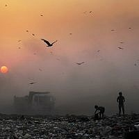 FILE- In this Oct. 17, 2014, file photo, a thick blanket of smoke is seen against the setting sun as young ragpickers search for reusable material at a garbage dump in New Delhi, India (AP Photo/Altaf Qadri, File)