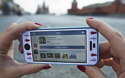 A user of Russia's leading social network internet site VKontakte, poses holding an iPhone showing the account page of Pavel Durov, the former CEO and founder of VKontakte, in Red Square in Moscow, Russia, Wednesday, April 23, 2014 (AP Photo/Pavel Golovkin)