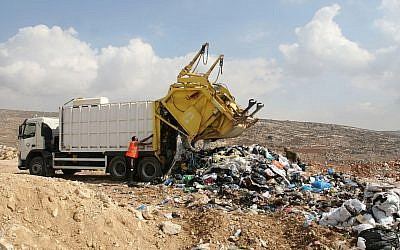 Illustrative: Palestinian workers try to remove scrap iron from an illegal garbage dump near the West Bank city of Ramallah. October 27, 2011. (Issam Rimawi/FLASH90)