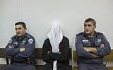 Ben Deri, center, a Border Police officer accused of shooting to death a Palestinian man during clashes in Betunia in the West Bank, seen during a hearing at the District Court in Jerusalem on December 30, 2014. (Yonatan Sindel/Flash90)