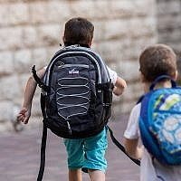 Illustrative: Israeli kids wearing school bags for first day of school outside their home in Jerusalem (Yonatan Sindel/Flash90)