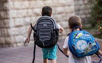 Illustrative: Israeli kids wearing school bags for first day of school outside their home in Jerusalem (Yonatan Sindel/Flash90)