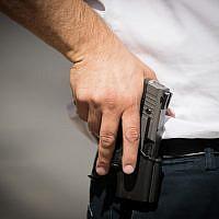 An illustration of a man holding a pistol on July 14, 2017. (Yonatan Sindel/Flash90)