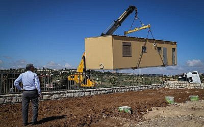 Illustrative: A crane lowers a caravan to the ground in a new settlement meant to resettle the evacuees of the illegal Netiv Ha'avot outpost in the Etzion bloc in the West Bank, on May 9, 2018. (Gershon Elinson/Flash90)