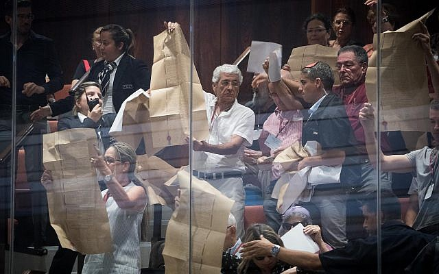 Activists wave copies of the Declaration of Independence during a special session about the nation-state law at the Knesset on August 8, 2018. (Yonatan Sindel/Flash90)