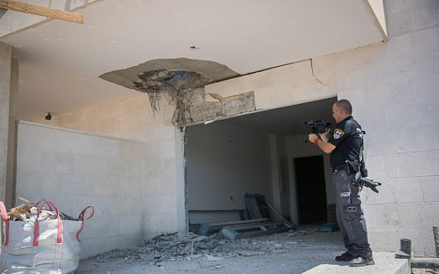 Un officier de police inspecte les dégâts sur un chantier de construction dans la ville de Sderot, au sud d'Israël, près de la frontière de Gaza suite à une roquette, le 9 août 2018. (Yonatan Sindel / Flash90)