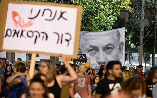 Demonstrators hold up signs at a Tel Aviv rally demanding security for residents of Israel's south on August 18, 2018. (Gili Yaari/Flash90)