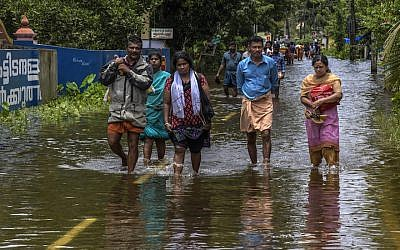 Locals cross flood water en route to  Chengannur on August 20, 2018 in Kerala, India. (Atul Loke/Getty Images/via JTA)