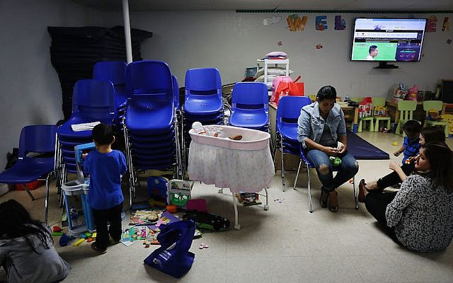 Recently arrived migrant families speak with volunteers at the Catholic Charities Humanitarian Respite Center on June 21, 2018 in McAllen, Texas. (Spencer Platt/Getty Images/via JTA)
