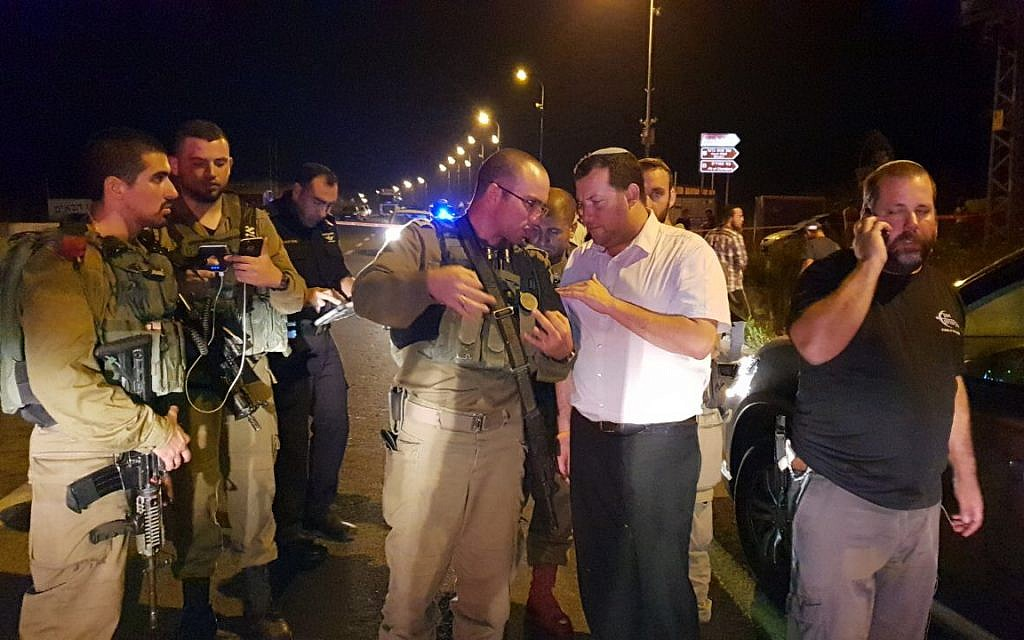 Samaria Regional Council Chairman Yossi Dagan (2nd right) speaks with a soldier at the scene where an Israeli woman was run over and killed by a Palestinian driver, near the northern West Bank settlement outpost of Havat Gilad on August 16, 2018. (Roi Hadi/Samaria Regional Council)