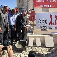 Former Arkansas governor Mike Huckabee (R) lays bricks at a housing complex in the West Bank settlement of Efrat on August 1, 2018. (Jacob Magid/Times of Israel)