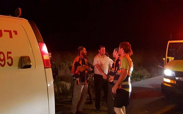 Samaria Regional Council Chairman Yossi Dagan speaks with paramedics at the scene of a suspected car-ramming attack near the northern West Bank settlement outpost of Havat Gilad on August 16, 2018. (Roi Hadi/Samaria Regional Council)