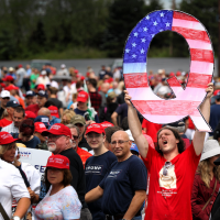 """David Reinert holds up a large """"Q"""" sign, representing QAnon, a conspiracy theory group, while waiting in line to see President Donald Trump at a rally in Wilkes-Barre, Pa., Aug. 2, 2018. (Rick Loomis/Getty Images via JTA)"""